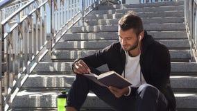 Der ruhige Kerl liest ein Buch, das auf den Schritten sitzt stock video