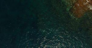 Der ruhige See wirft leicht seine Wellen auf der Steinküste stock video footage