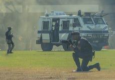 Der südafrikanische Polizeidienst - Polizisten und Cassper zwar angesehen dem orange Dunst einer orange Rauchgranate Stockbilder