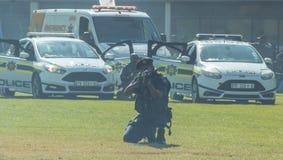 Der südafrikanische Polizeidienst - Polizisten und Cassper zwar angesehen dem orange Dunst einer orange Rauchgranate Lizenzfreies Stockfoto