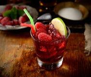 Der Saft von frischen Himbeeren mit Eis in einem Glas, in einer Platte der Frucht und im Zucker im Hintergrund Stockbilder