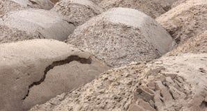 Der Sand liegt in den Haufen, die mit dem LKW zum Gebäude geholt werden lizenzfreies stockfoto