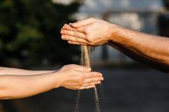 Der Sand wird aus den Händen von Männern heraus in Frauen ` s Hände gegossen stockfoto