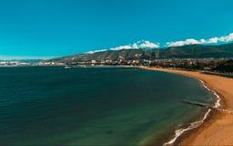 Der sandige Strand des Morgens Gelendzhik-Bucht im Frühjahr mit Blick auf den zentralen Pier und die Wohngebäude Gelendzhik, Rus Lizenzfreie Stockfotografie