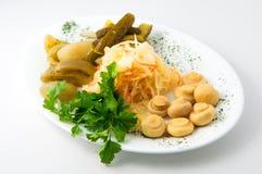 Der Satz von Essiggurken auf der Platte mit Gurken, Tomaten, Pilze, Sauerkraut Stockfotografie