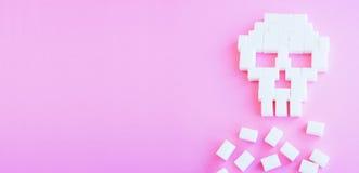 Der Schädel hergestellt von den Zuckerwürfeln abbrüche Rosa Hintergrund Lizenzfreie Stockbilder