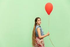 Der schöne blonde Jugendliche, der die Kamera, roten Ballon auf einem grünen Hintergrund halten betrachtet Stockfotos