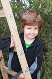 Der schöne blonde Junge kletterte Leitern Stockfoto