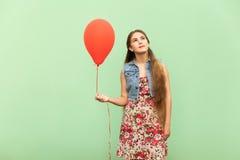 Der schöne blonde träumende Jugendliche, mit roten Ballons auf einem grünen Hintergrund Lizenzfreie Stockbilder