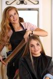 Der schöne blonde weibliche Friseur, der Kamm halten und das Haar schließen zu Stockbild