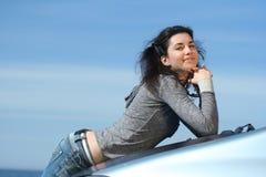 Der schöne Brunette auf einer Autoverkleidung Stockfoto