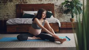 Der schöne Brunette, der Mutter erwartet, tut, die Übungen ausdehnend, die vorwärts zu übendem Yoga des Beines für Mutter-zu verb stock video footage