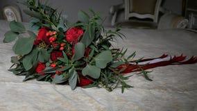 Der schöne Hochzeitsblumenstrauß von roten Rosen und von Pfingstrosen, die mit Bändern eingewickelt werden, liegt auf dem Bett Se stock video footage