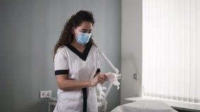 Der schöne kaukasische Cosmetologist bereitet sich für den Kunden vor - setzend auf die Maske und die transparenten Handschuhe stock footage