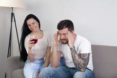 Der schöne trinkende Wein des jungen Mädchens, der auf der Couch sitzen, und ihr Freund ist das Sitzen frustriert Er hat Kopfschm lizenzfreie stockfotos