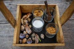 Der schöne Weinleseholzkistekorb, der Zuckergläser halten und der Löffel für Kaffee und Tee mit Meer schälen Dekoration auf Holzt Stockbild