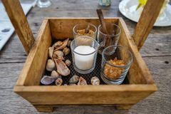 Der schöne Weinleseholzkistekorb, der Zuckergläser halten und der Löffel für Kaffee und Tee mit Meer schälen Dekoration auf Holzt Stockfotografie