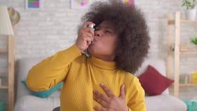 Der schönen ist plötzlicher asthmatischer Angriff Afroamerikanerafrofrisur des Porträts der Gebrauch des Sprays langsames MO stock footage