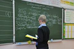 Der Schüler führt das Brett der Aufgabe in der Schule an der Lektion der russischen Sprache durch lizenzfreies stockfoto