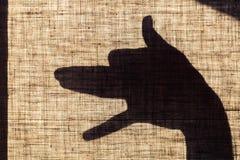 Der Schatten der Hand und der Finger in Form eines Hundes formte Kennzeichen auf Flachssegeltuch Stockbilder