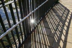 Der Schatten des Balkons, der im Sonnenlicht Streifen mit der Eisenbahn befördert Stockfotografie
