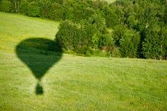 Der Schatten des Ballons auf dem Hintergrund einer grünen Wiese lizenzfreie stockbilder