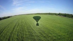 Der Schatten des Ballons auf einem grünen Feld Stockbild