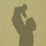 Der Schatten des Vaters hält Baby lizenzfreie stockfotografie