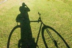 Der Schatten eines Fahrrades und der Leute auf der grünen Farbe des Grases als dem Hintergrund Stockfotografie