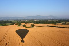 Der Schatten eines Heißluftballons, der über ländliches Ackerland fliegt Stockbild