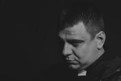 Der Schauspieler unter dem Mantel eines Priesters gegen einen dunklen Hintergrund Lizenzfreie Stockfotos