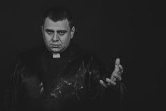 Der Schauspieler unter dem Mantel eines Priesters gegen einen dunklen Hintergrund Stockbild