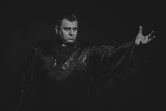 Der Schauspieler unter dem Mantel eines Priesters gegen einen dunklen Hintergrund Lizenzfreie Stockbilder