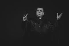 Der Schauspieler unter dem Mantel eines Priesters gegen einen dunklen Hintergrund Lizenzfreies Stockfoto