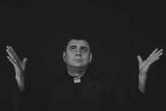 Der Schauspieler unter dem Mantel eines Priesters gegen einen dunklen Hintergrund Lizenzfreie Stockfotografie