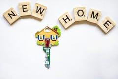 Der Schlüssel ist in Form von dem Haus auf einem weißen Hintergrund und den Holzklötzen mit dem Wort unser Haus Lizenzfreies Stockfoto