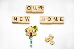 Der Schlüssel ist in Form von dem Haus auf einem weißen Hintergrund und den Holzklötzen mit dem Wort unser Haus Lizenzfreies Stockbild