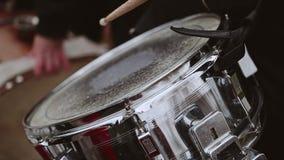 Der Schlagzeuger im Orchester bereitet sich vor und fängt an, auf der Führungstrommel zu spielen stock video