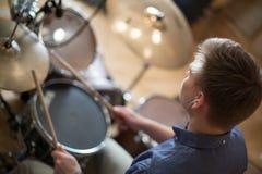 Der Schlagzeuger mit Kopfhörern spielt die Trommelausrüstung Stockbild