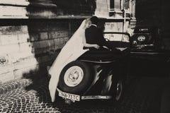 Der Schleier der Braut hängt unten, während sie mit Bräutigam auf einem Retro- Auto sitzt Stockfotografie