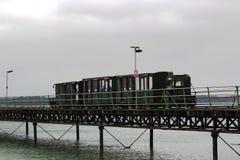 Der Schmalspurzug, der die Länge der tragenden Passagiere Hythe-Piers nach und von der Fähre nach genommenes Southampton laufen l lizenzfreies stockfoto