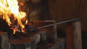 Der Schmied, der ein Leder verwendet, brüllt, Kohlen auflockernd und zieht ein glühendes Billet aus stock video footage