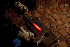 Der Schmied, der manuell das flüssige Metall schmiedet stockbilder