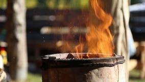 Der Schmied legt die Kohle in den Ofen stock footage