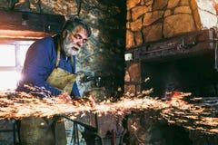 Der Schmied, der manuell das flüssige Metall schmiedet stockfotografie