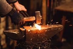 Der Schmied, der manuell das glühende Metall auf dem Ambosse in der Schmiede mit Funkenfeuerwerken schmiedet lizenzfreies stockfoto