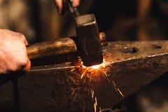 Der Schmied, der manuell das glühende Metall auf dem Ambosse in der Schmiede mit Funkenfeuerwerken schmiedet stockfotografie