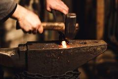 Der Schmied, der manuell das glühende Metall auf dem Ambosse in der Schmiede mit Funkenfeuerwerken schmiedet lizenzfreie stockbilder