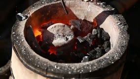 Der Schmied richtet den Tiegel im Ofen mit einem Poker gerade stock video footage