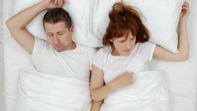Der schnarchende Mann, der heraus lautes erdrosseln, seine Frau oben während der lauten Nacht aufweckend und sie schließen Ohren  stock video